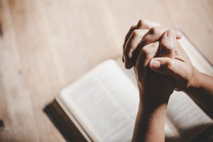 hands praying to god with the bible.