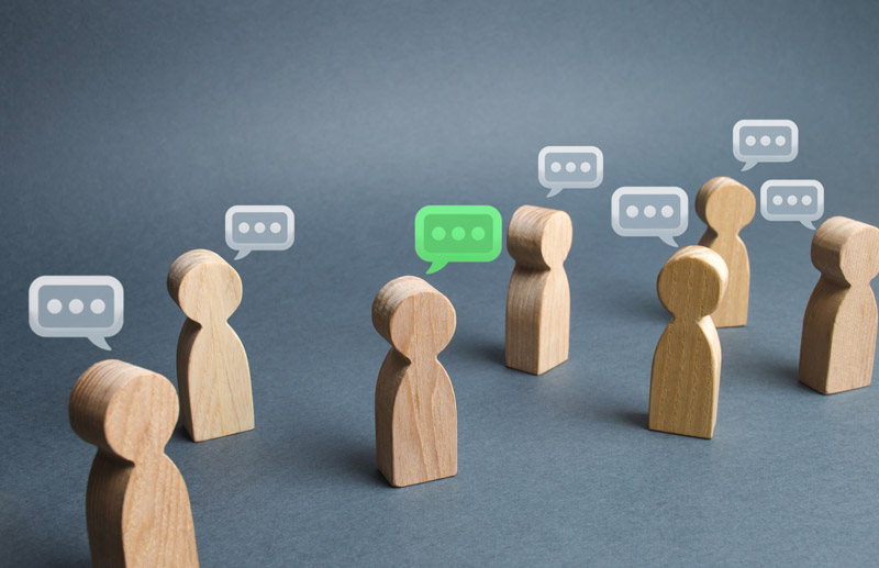 Wooden block figures with text bubbles over their heads