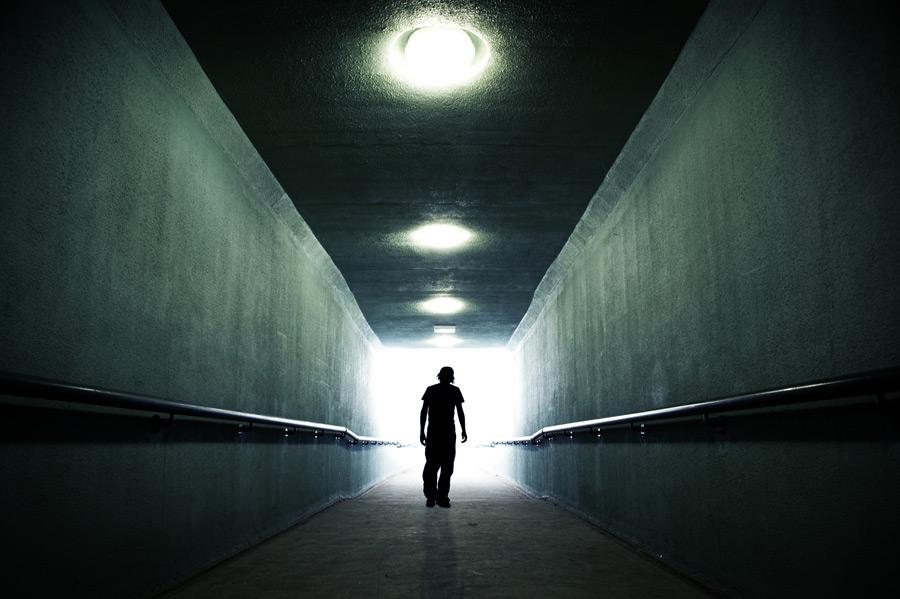 An-american-youth-walking-in-a-dark-tunnel